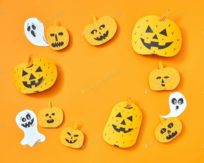 Scary frame from paper handcraft paper pumpkins and ghosts on an orange background with copy space