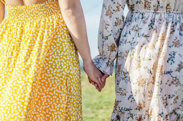 Women hold their hands outdoors rear view. Friendship or romance concept