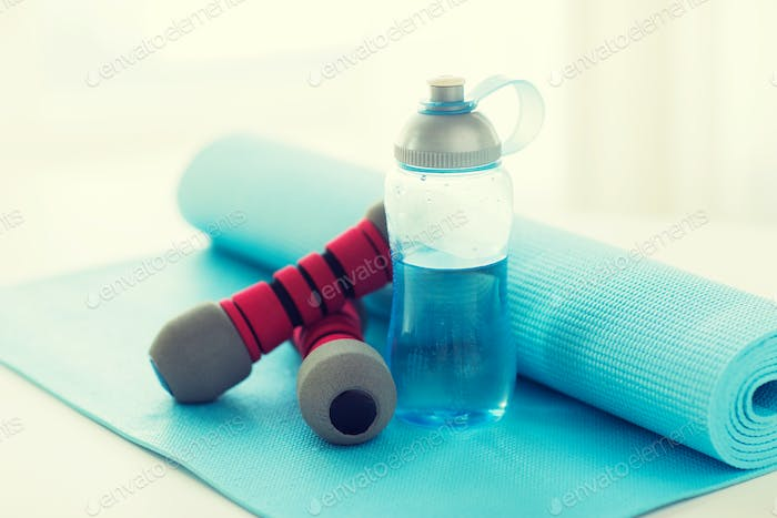 close up of bottle, dumbbells and sports mat