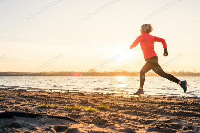 Woman beach running at sunrise, lake coastline