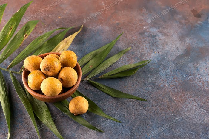 Tropical fruit longan in the bamboo basket on stone background