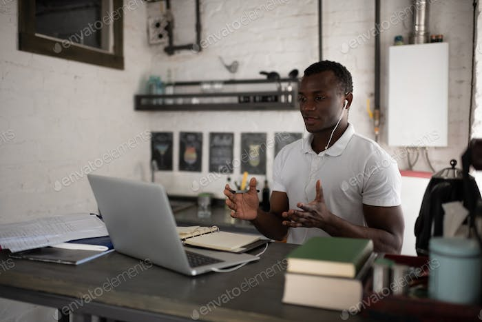 Smart black student discussing assignment during online lesson at home