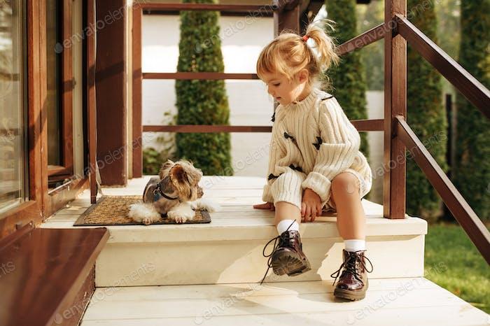 Niño con perro divertido están sentados en las escaleras