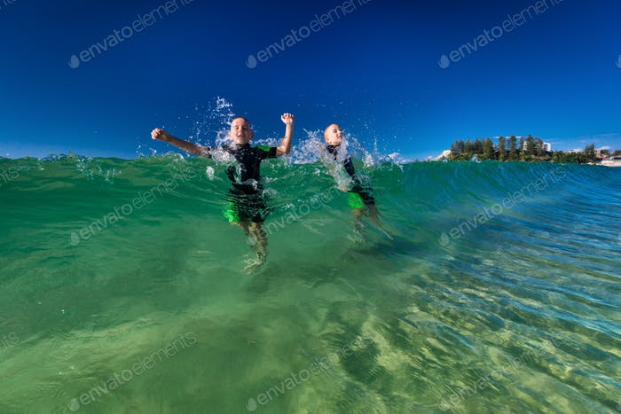 Boys swimming and playing with large ocean waves