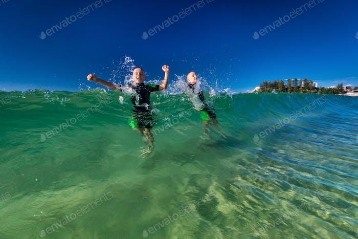 Jungen schwimmen und spielen mit großen Meereswellen