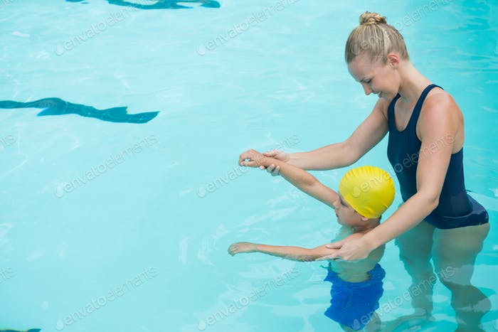 Female instructor training young boy in pool
