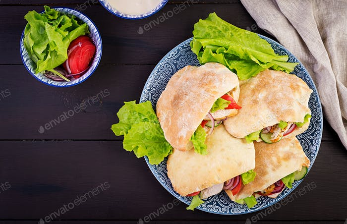 Pita stuffed with chicken, tomato and lettuce on wooden background. Middle Eastern cuisine. Top view