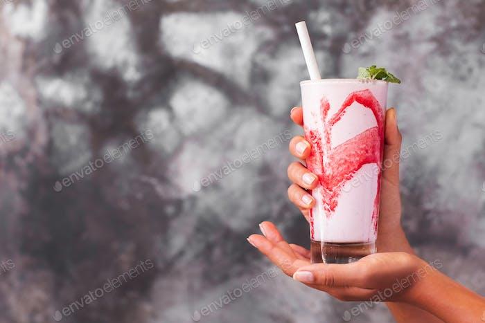 Glas frischer kalter Frappe oder Frappuccino mit rotem Erdbeersirup in den Händen der Frau