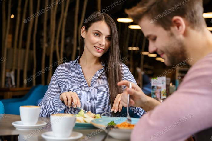 Attractive young couple having lunch at the cafe indoors