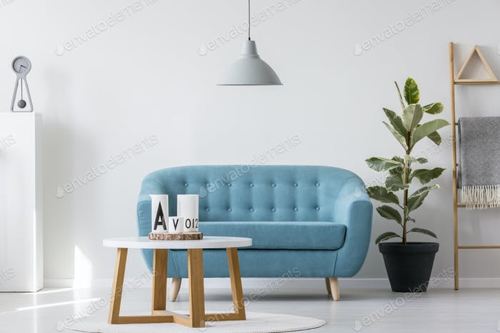 White wooden coffee table next to blue elegant couch in bright l