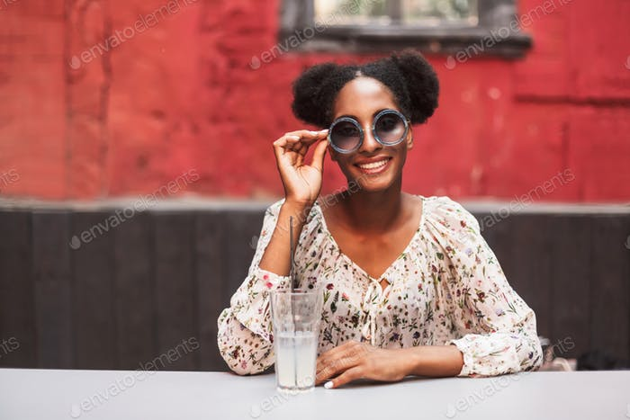 Smiling african girl in blouse and sunglasses joyfully looking i