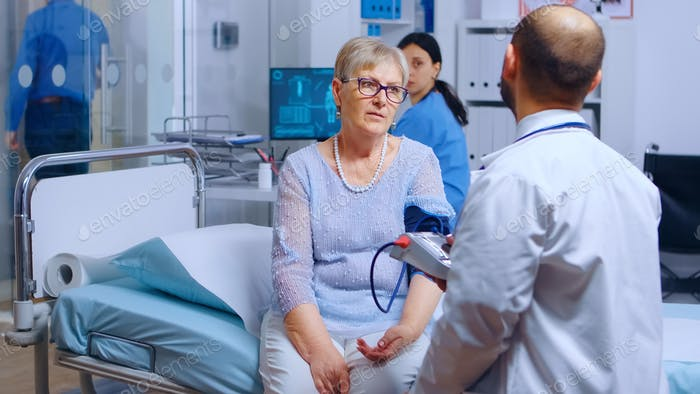 Praktiker misst ältere pensionierte Frau Blutdruck