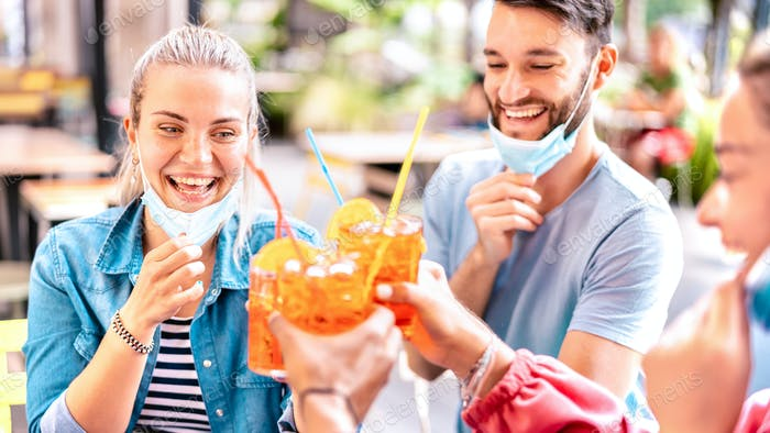 Friends drinking at cocktail bar with open face masks