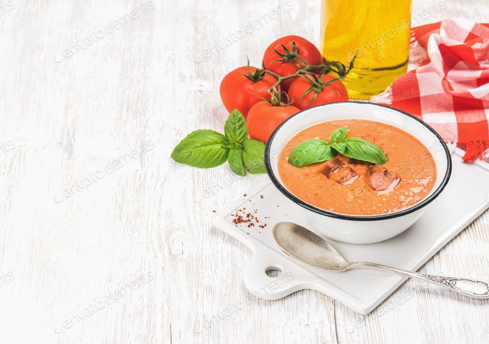 Cold gazpacho soup with ice, basil and tomatoes, copy space