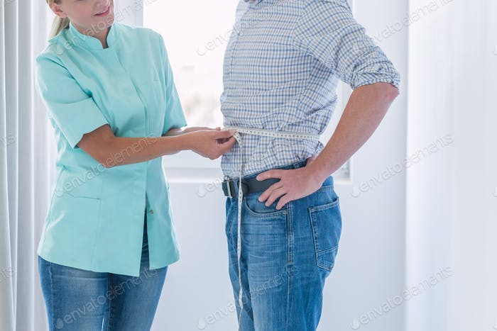 Young helpful dietitian measures the patient's waist circumference during the examination