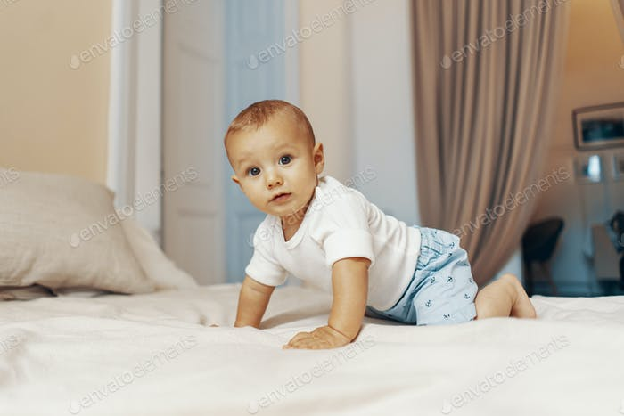 Portrait of a crawling baby on the bed