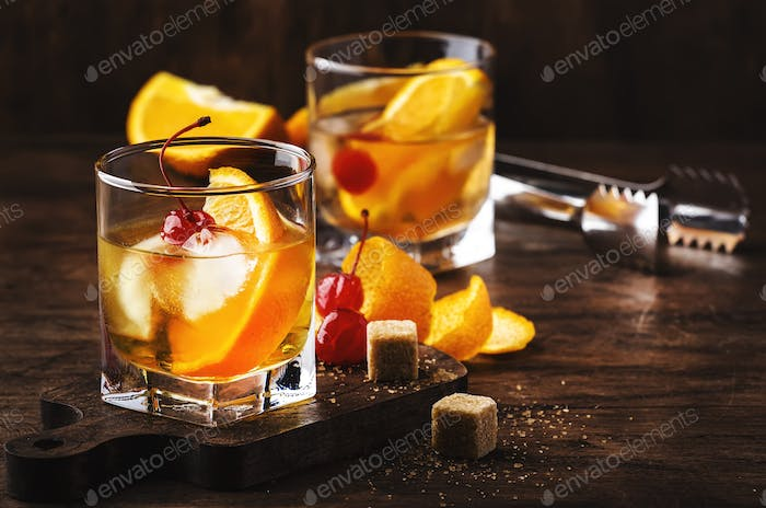 Old fashioned cocktail with bourbon, cane sugar, orange slice, cherry and orange peel