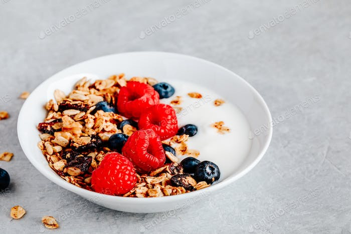 Healthy breakfast bowl homemade granola with fresh blueberry and raspberry