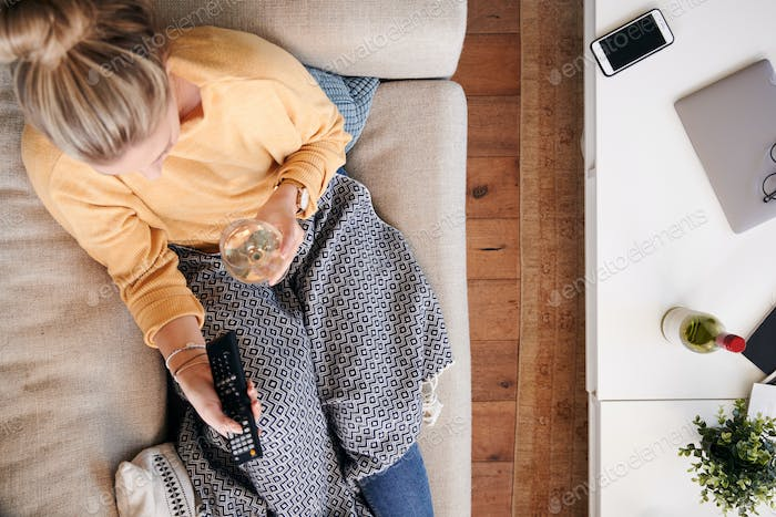 Overhead Shot Looking Down On Woman At Home Lying On Sofa Watching Television And Drinking Wine