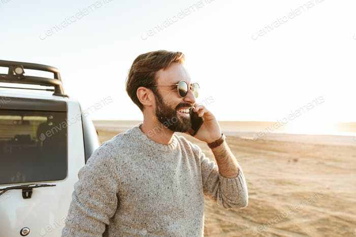 Smiling handsome young man using mobile phone