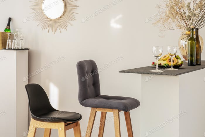Two stylish bar chairs nest to kitchen island with vine glasses and fruits