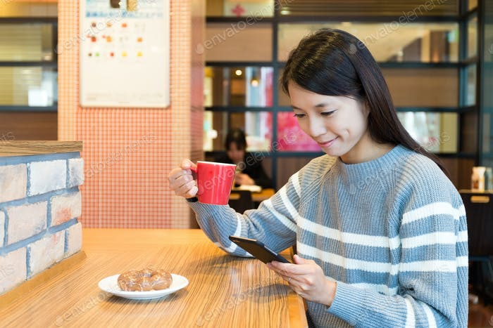 Woman enjoy her morning coffee with mobile phone
