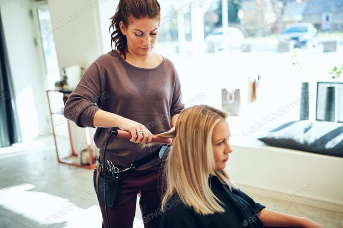 Young woman having her hair straightened by a hairdresser