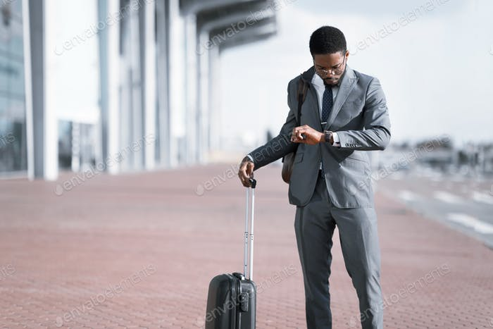 Businessman With Travel Suitcase Waiting For Delayed Flight At Airport