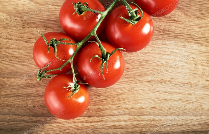 Branch of red cherry tomatoes organic wooden background.
