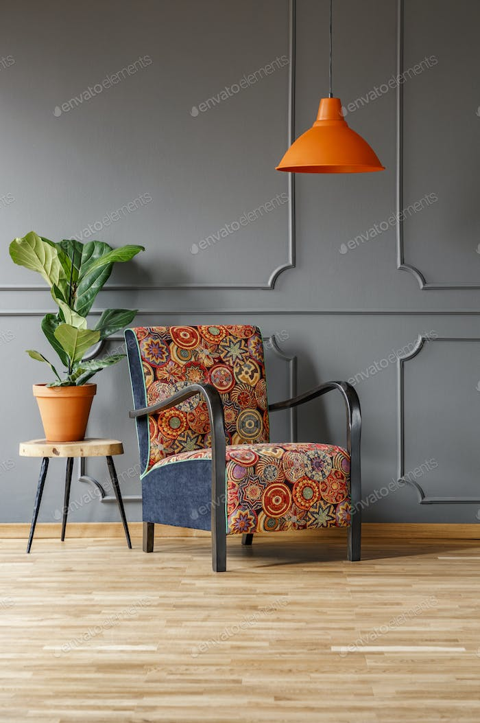 Plant on table next to patterned armchair under orange lamp in g