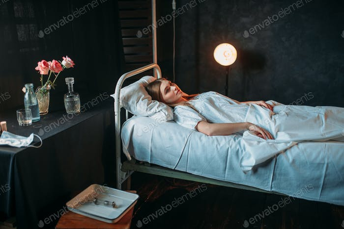 Young ill woman lying in hospital bed