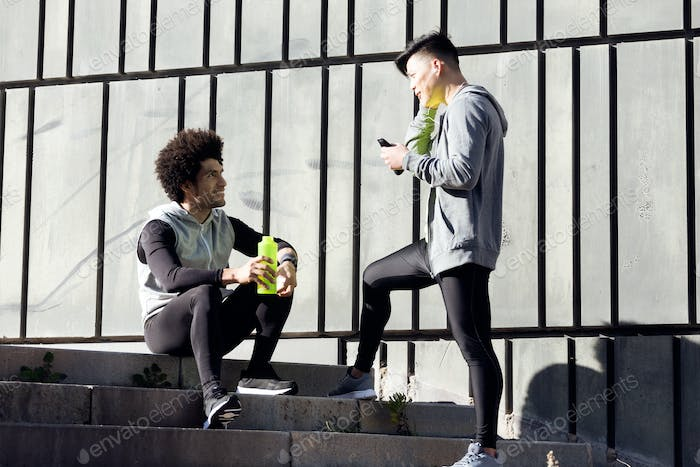 Two fit and sporty young men relaxing and stretching after work