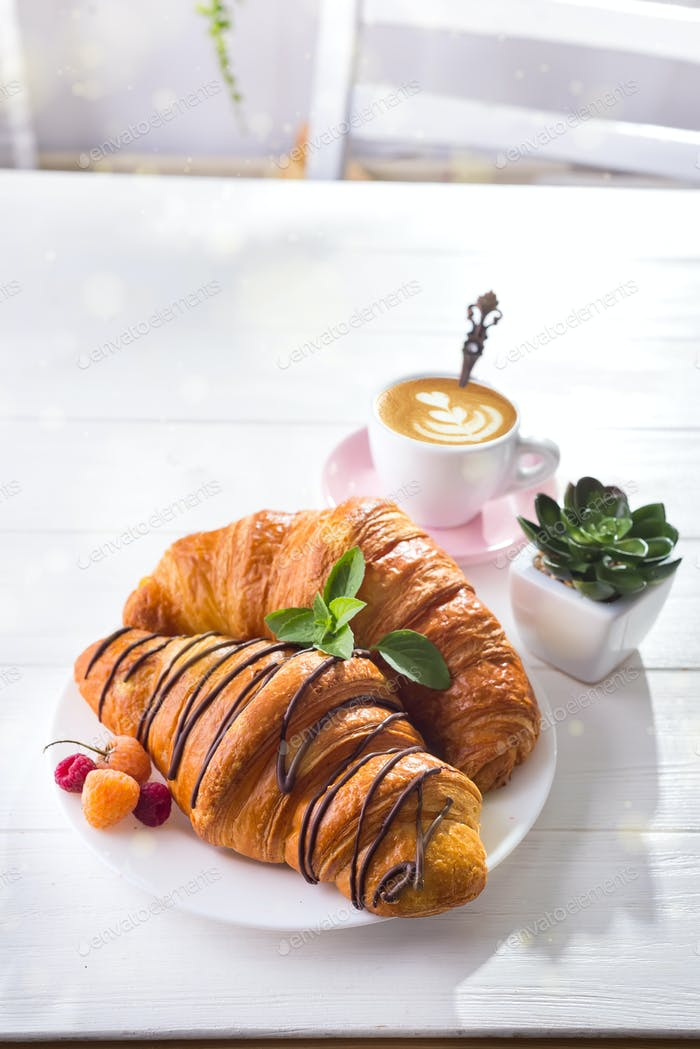 Fresh Croissant with berries and cup of coffee for breakfast, suculent flowers