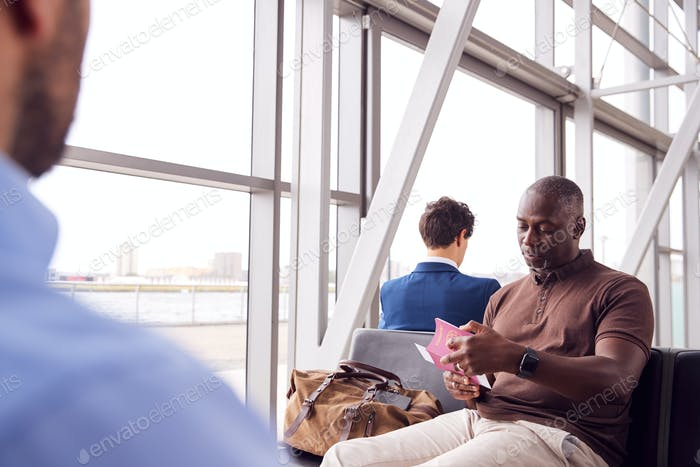 Male Passenger In Airport Departure Lounge Checking Travel Documents
