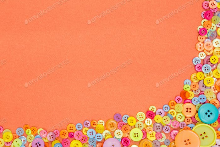 Colourful buttons on an orange background with copy space.