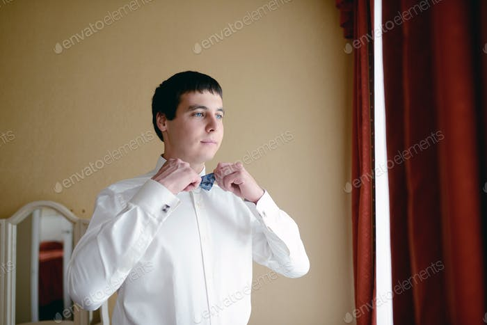 Groom is wearing a bowtie indoors