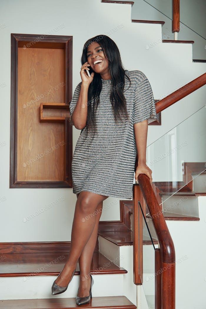 Elegante Frau am Telefon in der Treppe sprechen