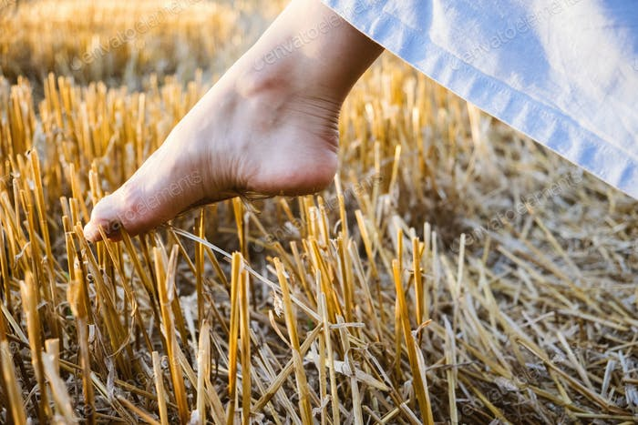 Overcome obstacles depression concept. A woman's bare foot makes a step over a sharp prickly