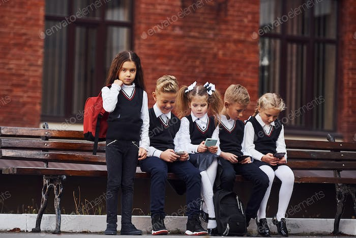 Group of kids in school uniform sits on the bench outdoors together near education building