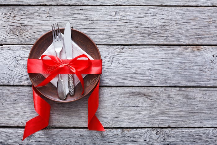 Valentine day background, cutlery on plate with ribbon on wood