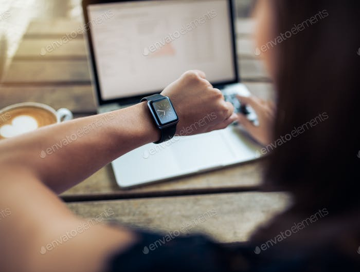 Woman checking time on her smartwatch