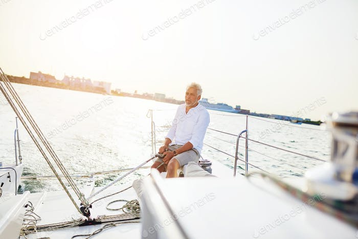 Mature man out sailing on a sunny afternoon
