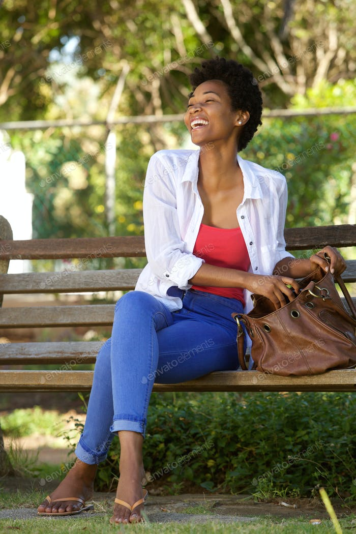 Smiling african woman sitting on a park bench with a bag