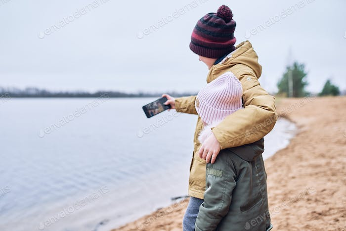 A boy in a yellow jacket and small girl is standing on the beach and made selfie