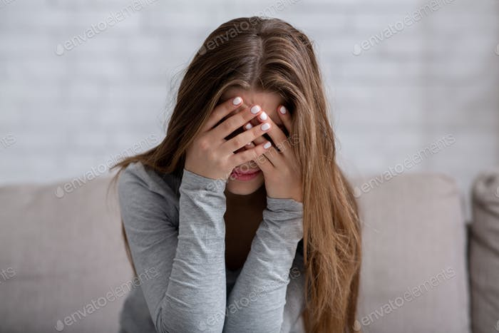 Millennial woman covering her face with hands and crying, feeling depressed or stressed