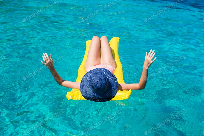 Frau entspannt auf aufblasbarer Matratze im Meer