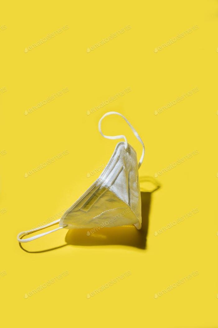 White medicine respirator KN95 mask over yellow