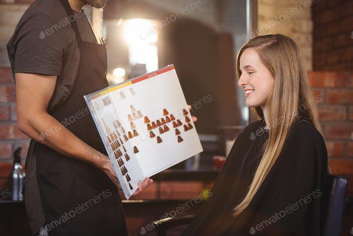 Frau Auswahl einer Haarfarbe mit Stylist