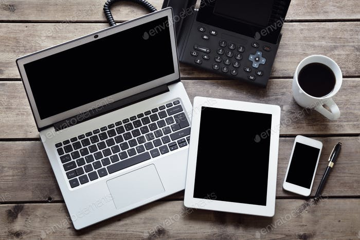 Open laptop with white digital tablet and smartphone on desk fro
