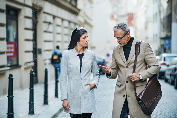 Man and woman business partners walking outdoors in city of Prague, talking.